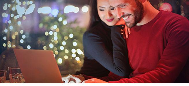Ein Paar tätigt am Computer Weihnachtseinkäufe
